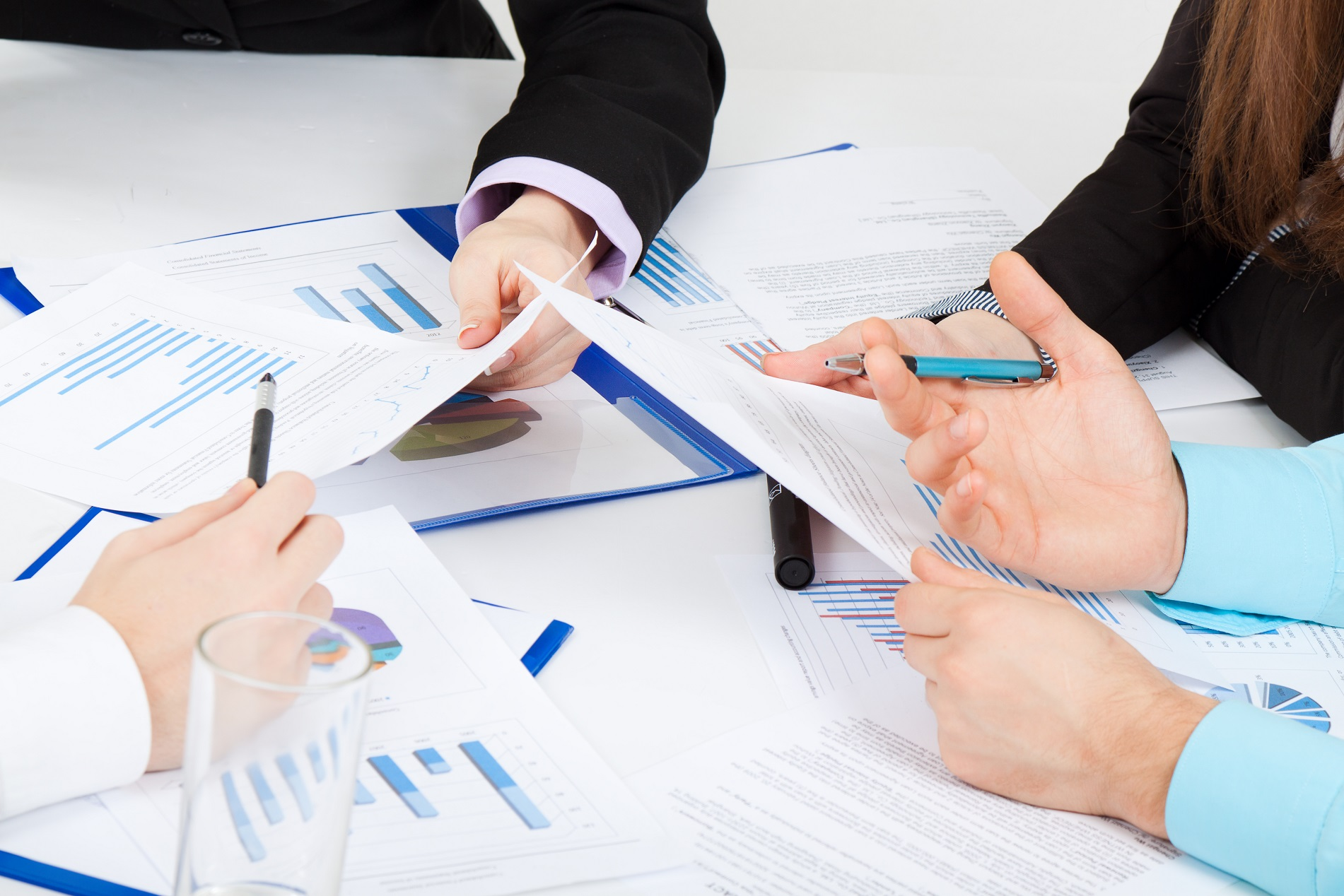 Businesspeople sitting at desk working in team together with documents sign up contract, businessmen holding financial charts, graph, folder with papers, explain business plan
